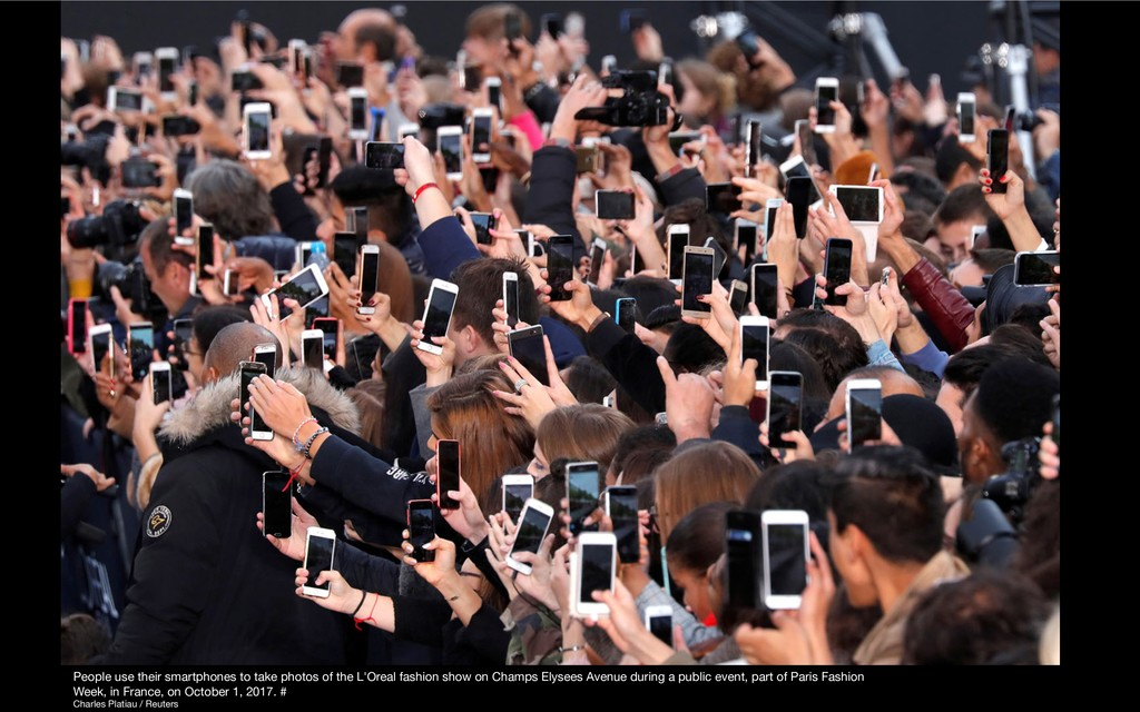 People use their smartphones to take photos of ...