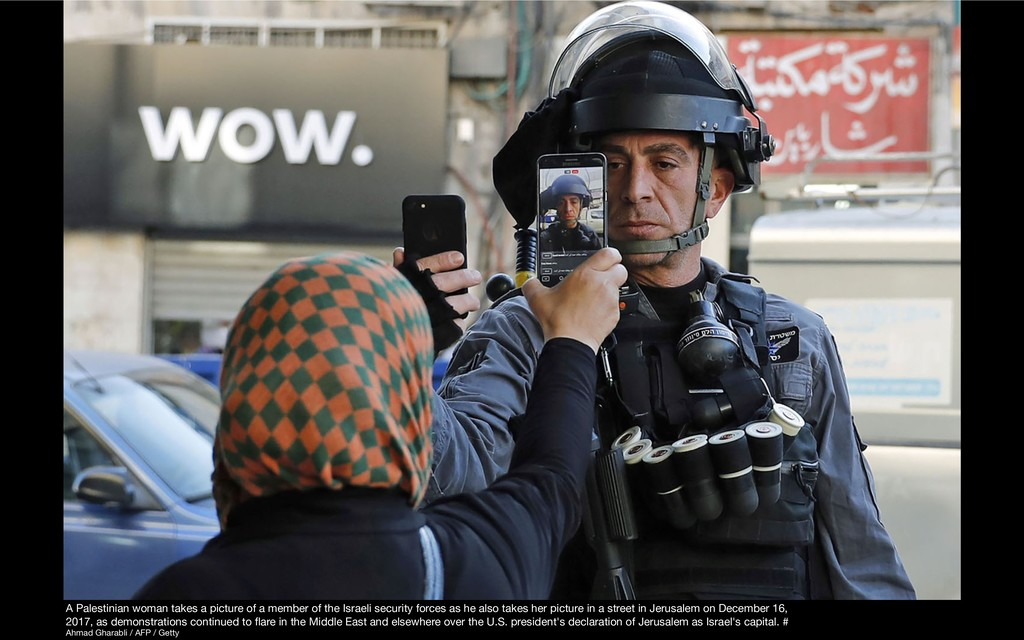 A Palestinian woman takes a picture of a member...